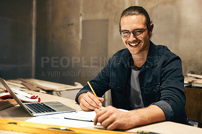 Buy stock photo Portrait of a focused young male carpenter working on a project inside of a workshop at night