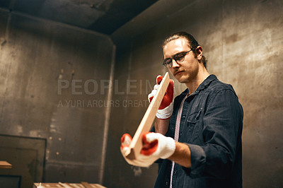 Buy stock photo Cropped shot of a focused young male carpenter holding and examining a piece of wood while working inside of a workshop at night