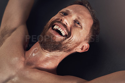 Buy stock photo Shot of a handsome young man smiling and feeling cheerful after working out indoors