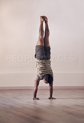 Buy stock photo Full length shot of an athletic young man doing a hand stand in studio
