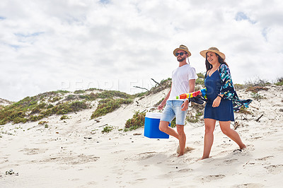 Buy stock photo Shot of a young couple carrying a cooler box and umbrella at the beach