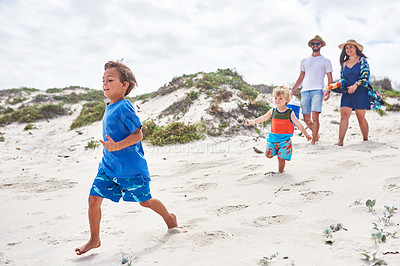 Buy stock photo Shot of two adorable little boys running along the beach with their parents in the background