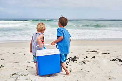 Buy stock photo Rearview shot of two little boys carrying a cooler box at the beach