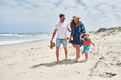 Buy stock photo Shot of an adorable little boy walking with his parents along the beach