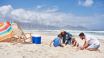 Buy stock photo Shot of a happy family building sandcastles together at the beach