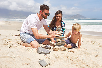 Buy stock photo Shot of a little boy and his parents balancing a stack of stones together at the beach