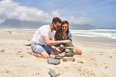 Buy stock photo Shot of a young couple balancing a stack of stones together at the beach