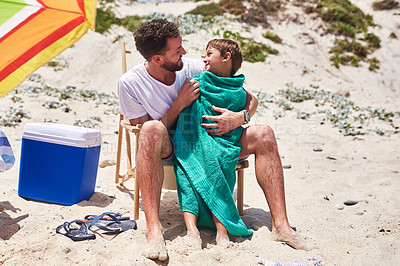 Buy stock photo Shot of a father wrapping his little son in a towel at the beach