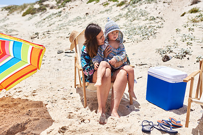 Buy stock photo Shot of a mother and her little son sitting on a deck chair at the beach