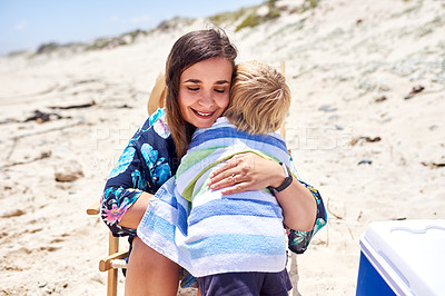 Buy stock photo Shot of a mother hugging her little son at the beach
