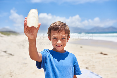 Buy stock photo Portrait of an adorable little boy holding a seashell at the beach