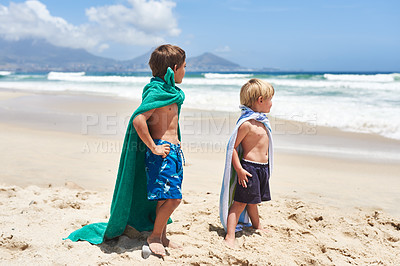 Buy stock photo Shot of two adorable little boys standing with towels wrapped around them at the beach