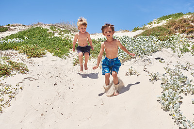 Buy stock photo Shot of two adorable little boys playing at the beach
