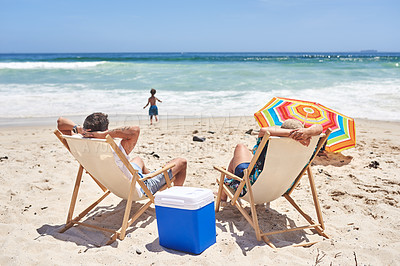 Buy stock photo Shot of a mother and father relaxing on deck chairs while their two little sons play at the beach