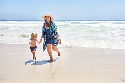 Buy stock photo Shot of a mother and her little son walking together along the beach