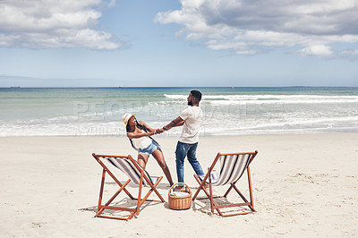 Buy stock photo Shot of an affectionate young couple enjoying their date at the beach