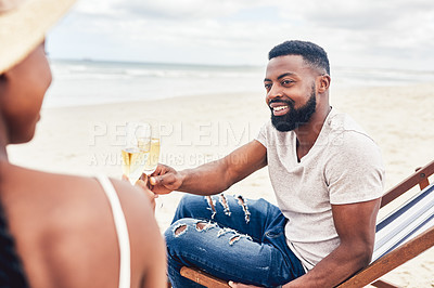 Buy stock photo Shot of a happy young couple enjoying drinks while relaxing on the beach