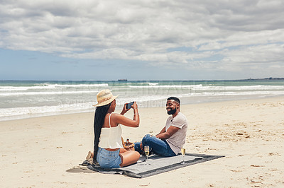 Buy stock photo Shot of a woman taking a picture of her boyfriend while relaxing on the beach
