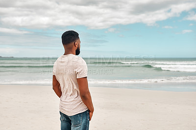 Buy stock photo Rearview shot of a young man spending some time at the beach