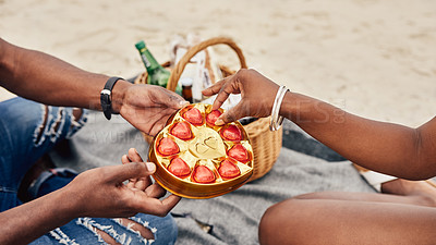 Buy stock photo Closeup shot of an unrecognisable couple having a picnic together at the beach