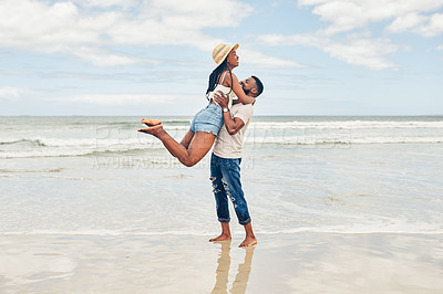Buy stock photo Shot of a young couple spending some time together at the beach