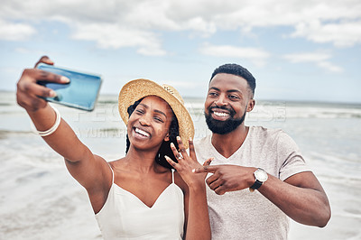 Buy stock photo Shot of a young couple taking selfies on the beach after their engagement