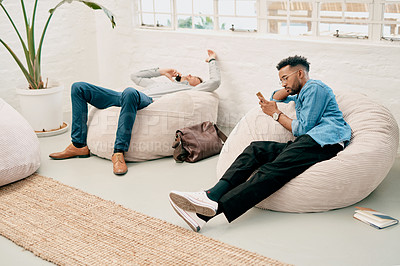 Buy stock photo Full length shot of two handsome young businessmen sitting on bean bags and using their cellphones in the office