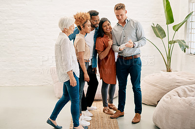 Buy stock photo Full length shot of a diverse group of businesspeople standing together in the office and looking at a cellphone