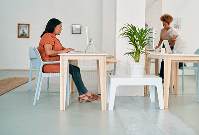 Buy stock photo Full length shot of an attractive young businesswoman sitting and using her computer in her coworking office space