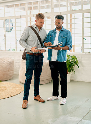 Buy stock photo Full length shot of two handsome young businessmen standing together and having a discussion in the office