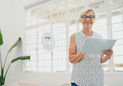 Buy stock photo Portrait of a senior businesswoman using a digital tablet in a modern office
