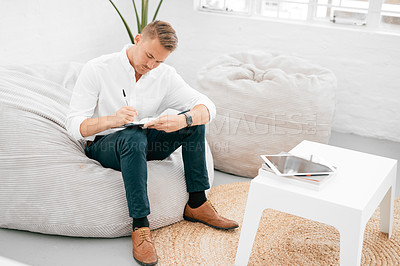 Buy stock photo Shot of a young businessman writing in a notebook in a modern office