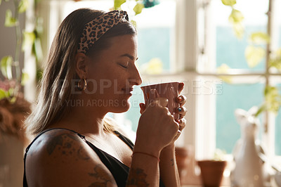 Buy stock photo Shot of a young woman having a relaxing coffee break at home