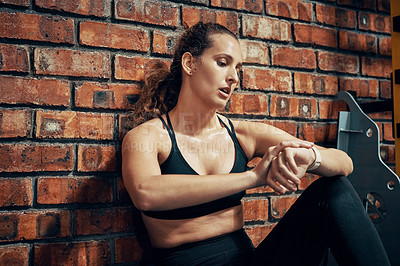 Buy stock photo Cropped shot of a woman checking the time after her workout at the gym