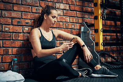 Buy stock photo Shot of a sporty young woman using her cellphone during her break at the gym