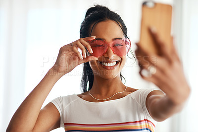 Buy stock photo Cropped shot of an attractive young blogger standing and wearing heart shaped glasses for a selfie with her cellphone