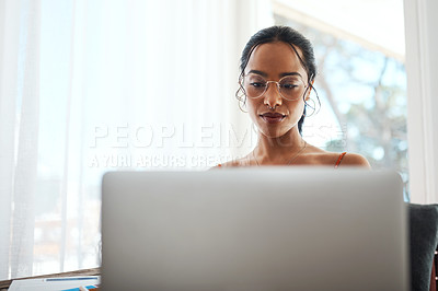 Buy stock photo Cropped shot of an attractive young businesswoman sitting in her home office and using her laptop