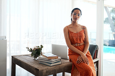 Buy stock photo Cropped portrait of an attractive young businesswoman sitting on her desk in her home office during a day off