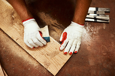 Buy stock photo Closeup of an unrecognizable male carpenter using sandpaper to smoothen out a piece of wood inside of a workshop at night