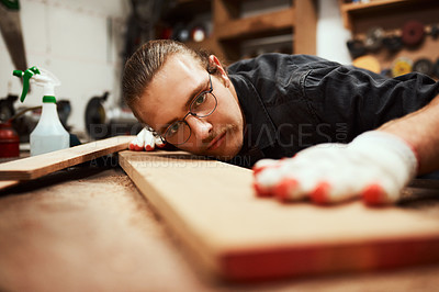 Buy stock photo Cropped shot of a focused young male carpenter blowing dust off of a piece of wood after sanding it inside of his workshop during the night