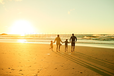 Buy stock photo Shot of a couple spending the day at the beach with their two kids