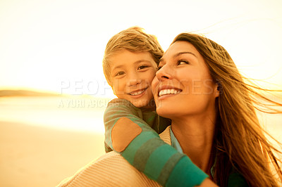 Buy stock photo Shot of a woman carrying her son on her back at the beach
