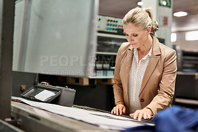 Buy stock photo Shot of a mature woman going over a blueprint while working in a factory