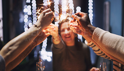 Buy stock photo Shot of a group of young friends playing with sparklers at a Christmas dinner party