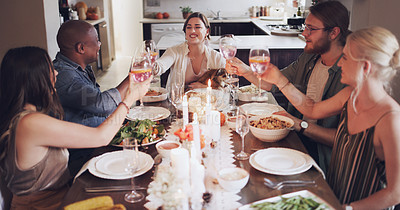 Buy stock photo Shot of a group of young friends toasting with wine at a Christmas dinner party