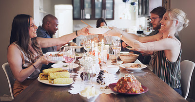Buy stock photo Shot of a group of young friends having a festive meal together at home