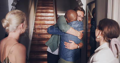 Buy stock photo Shot of a group of young men and women excitedly welcoming their friend home