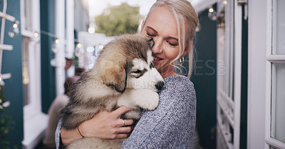 Buy stock photo Shot of young woman cuddling her adorable husky puppy during a social gathering at home