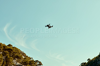 Buy stock photo Full length shot of a drone flying high in the sky