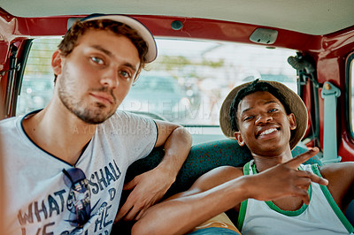 Buy stock photo Portrait of two young men sitting in the backseat of car while traveling together during the day